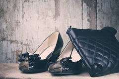 Women fashion shoes and bag. Women shoes and a bag on wooden background Royalty Free Stock Photos