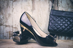 Women fashion shoes and bag. Women shoes and a bag on wooden background Royalty Free Stock Photography