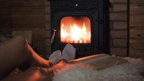 Women feet lie comfortably and warm by the warm fire of the fireplace