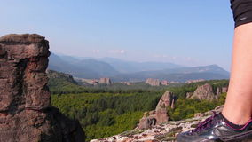 Women feet in sport shoes step on a rock, tourist admire the Belogradchik valley stock video footage