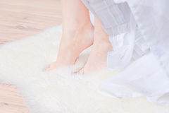 Women feet on a white fur Stock Photos
