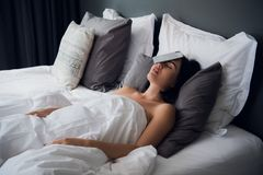 Women felt asleep with a mobile phone on her face at night In the bedroom at her house. She sleep without clean the. Women felt asleep with a mobile phone on her royalty free stock photography