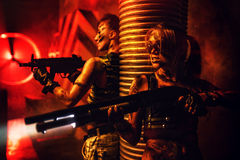 Women fighters team. Two women with big guns war fighting thriller concept. Dark red dramatic light and urban interior Stock Photography
