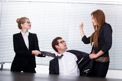 Women fighting for a man. Women fighting for a men in office Stock Photos