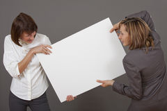 Women fighting over white board Stock Photos