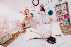Women Fighting with Pillows on White Interior. royalty free stock photography