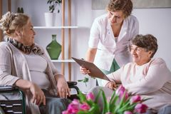 Women filling in the forms with their nurse in their retirement home. Elderly women filling in the forms with their nurse in their retirement home royalty free stock image