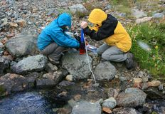 Women Filtering Water from Creek. Two women filtering water from Russet Creek in Garibaldi Provincial Park, British Columbia, Canada Stock Images