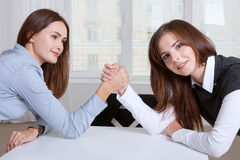 Women finance competitive worker while armwrestling Stock Photos