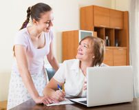 Women with financial documents and laptop at table Stock Photo