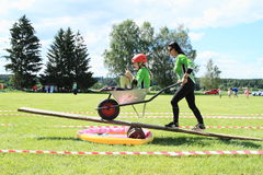 Women firefighters with wheelbarrow on see-saw. Women firefighters - girls running on contest with wheelbarrow on see-saw during firefighters competition (The Stock Image