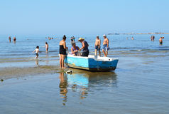 Women in Fishing Boat on the Beach of Durres, Albania. Durres, Albania - August 30, 2015: Women in an old fishing boat check the fishing net. Port Durres seen in Royalty Free Stock Image