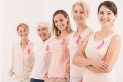 Symbol of breast cancer struggle. Women of five generations standing in a row wearing pink ribbons as the symbol of breast cancer struggle stock images