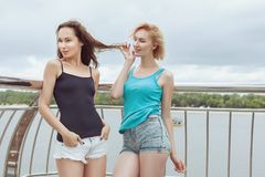 Women flirt with each other outdoors. Royalty Free Stock Photography