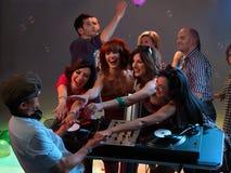 Women flirting with dj in night club. Sexy, young women dancing and flirting with the dj in a night club royalty free stock photography
