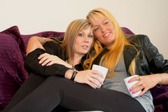 Women flirting. Two Young women flirting and drinking coffee royalty free stock image