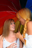 Women flirting. Two Young women flirting holding a Rainbow colored umbrella royalty free stock images