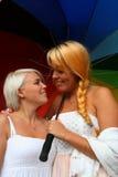 Women flirting. Two Young women flirting holding a Rainbow colored umbrella stock photos