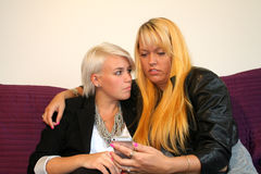 Women flirting. Two Young women reading a text message royalty free stock photo