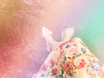 Women in flowers dress sit and dip feet in water Stock Photo