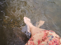 Women in flowers dress sit and dip feet in water Stock Photos