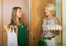Women with food purchases at threshold. Smiling females with food purchases in bags at threshold stock photos