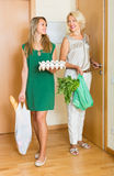 Women with food purchases at threshold Stock Photos