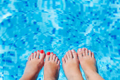 Women foot  splashing in swimming pool. Sexy women legs splashing in tropical swimming pool Royalty Free Stock Photo