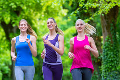 Women in forest running for sport. Three motivated women jogging in green forest royalty free stock photos