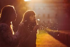 Women freedom and hope. Nature and harmony. Romantic sunset. Two young women taking and blowing a dandelion flower. Warm lighting