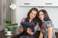Women friends chatting at home and using laptop to look at new p Royalty Free Stock Image