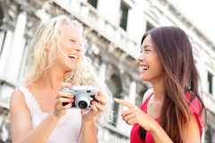 Women friends - girlfriends laughing having fun. Happy outside. Multiracial friends, Asian women and Caucasian blonde girl looking at pictures on camera, Travel Royalty Free Stock Photos