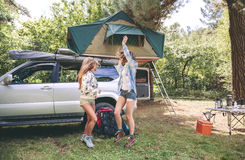 Women friends having fun in campsite into the forest. Young women friends having fun in a campsite into the forest. Leisure time and enjoyment concept stock images