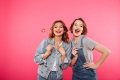 Women friends holding fake lips. Image of two funny women friends standing isolated over pink background. Looking camera holding fake lips Stock Photo
