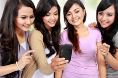 Women friends at home using handphone. Four beautiful young women friends at home using mobile phone together Stock Photo