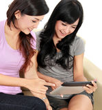 Women friends at home using tablet computer Stock Photography