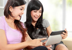 Women friends at home using tablet computer. Two beautiful young women friends at home using tablet computer and smiling Stock Photos