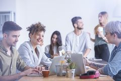 Women friends laughing. Two young women friends laughing during brainstorm at white office Royalty Free Stock Image