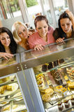 Women friends looking at cakes in cafe. Craving window display Royalty Free Stock Photos