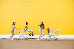 Women friends over yellow wall. Have fun with shopping trolley. Stock Photography