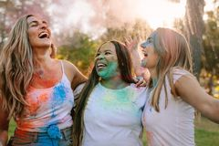 Women friends playing holi in a park royalty free stock photography