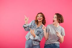 Women friends pointing to copyspace. Image of two women friends standing isolated over pink background pointing to copyspace Stock Image