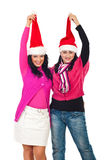 Women friends pulling Santa hats Stock Photo
