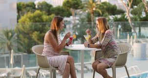 Women friends relax on vacation. The company of cheerful women sits at the table and drinks a cocktail against the background of the sea and palm trees. Women stock video