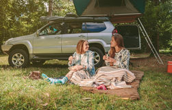 Women friends resting under blanket in campsite Royalty Free Stock Image