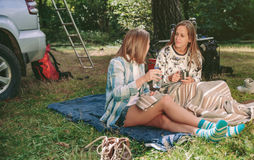 Women friends talking and resting under blanket. Happy young women friends talking and resting sitting under a blanket in campsite into the forest Royalty Free Stock Photography