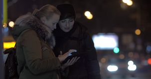 Women friends using tablet PC when waiting for bus in the street. Two young women discussing something using digital tablet while waiting for a bus at public stock video footage