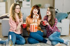 Women friendship, home party. Three beautiful funny young girl friends with popcorn in hands sitting on the floor in. Cozy room at home and looking on camera stock image