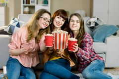 Women friendship, home party. Three beautiful funny young girl friends with popcorn in hands sitting on the floor in. Cozy room at home and looking on camera stock photography