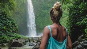 Women in front of tropical waterfall surrounded by lush green jungle. Falling water hitting water surface. Slight wind stock footage
